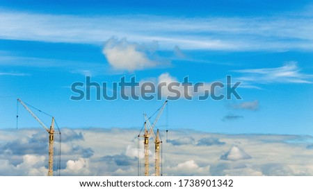 Construction cranes on a background of blue cloudy sky #1738901342