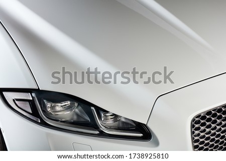 The headlight and bonnet of a white car. A modern and luxurious car. Royalty-Free Stock Photo #1738925810