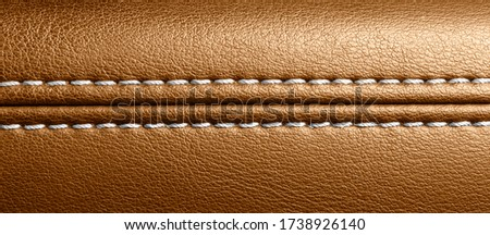 Car brown leather interior. Part of perforated leather door handle details. Orange Perforated leather texture background. Texture, artificial leather with stitching.  #1738926140