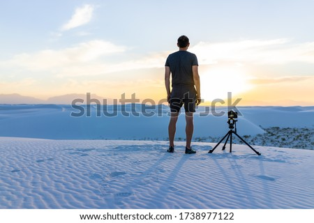 Young man professional photographer with camera tripod filming time lapse photography at White sands dunes national monument, New Mexico at sunset with Organ mountains view #1738977122