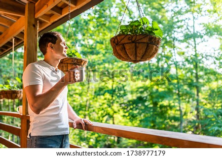 Hanging potted plant flowerpot with man drinking coffee tea mug cup on porch of log cabin cottage house with green color #1738977179
