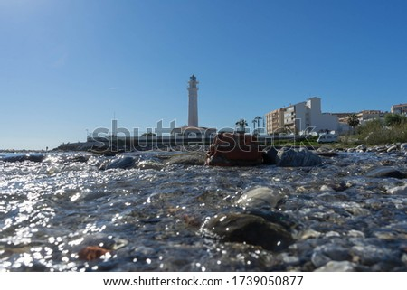 A closeup of the water of the ocean and a lighthouse in the background in Torrox Costa in Spain. #1739050877