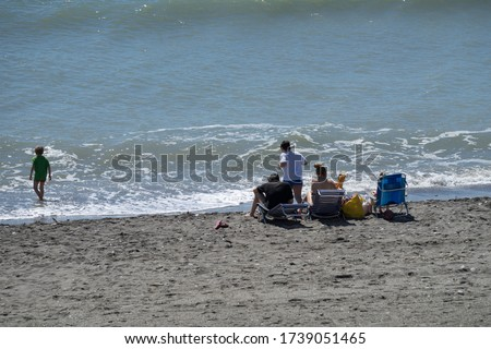 A family with two children play on the beach on a sunny day at the ocean in the holiday season. #1739051465