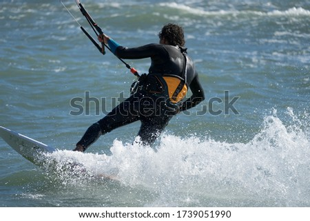 A kite surfer in a wild ocean with a heavy wind doing extreme sport. Splashing water from his surfboard. #1739051990