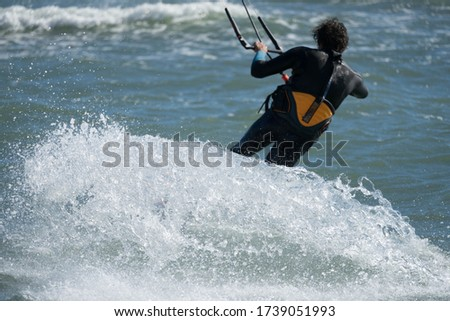 Big splashing water from a surfboard of a kite surfer doing his danger extreme sport. #1739051993