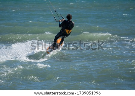 A professional kite surfer surfing over the ocean. #1739051996