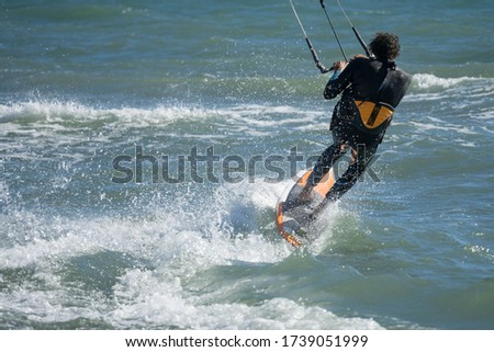 A kite surfer allmost falling and surfing over the ocean. #1739051999