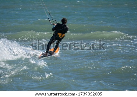 A professional kite surfer surfing over the ocean. #1739052005