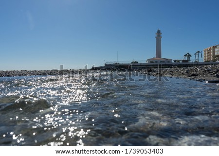 A closeup of the water of the ocean and a lighthouse in the background in Torrox Costa in Spain. #1739053403