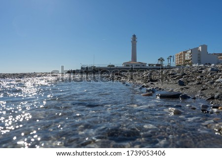 A closeup of the water of the ocean and a lighthouse in the background in Torrox Costa in Spain. #1739053406