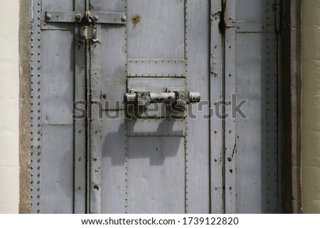 Locked on a padlock metal massive gray door. Symbolic Background #1739122820