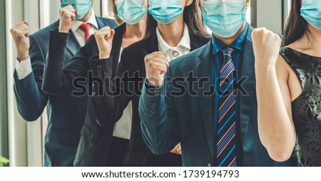 Confident business people with face mask protect from Coronavirus or COVID-19. Concept of help, support and collaboration together to overcome epidemic of Coronavirus or COVID-19 to reopen business. Royalty-Free Stock Photo #1739194793