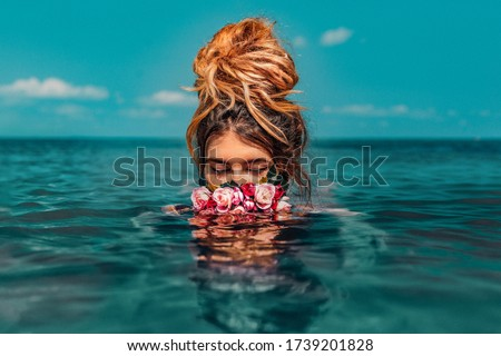 beautiful young woman swimming in sea with wreath conceptual fashion portrait  #1739201828