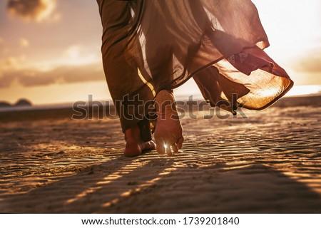 close up of woman feet walking onthe beach at sunset #1739201840