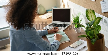 Focused african american teen girl student pupil writing notes in notebook distance learning studying online makes goals check list at home office. Remote college school education, elearning concept. #1739213264