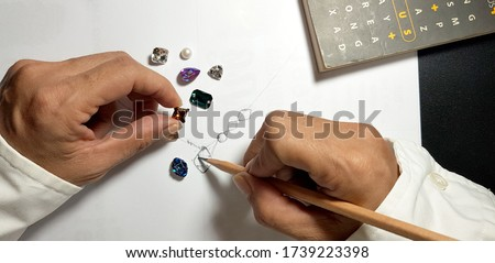 Jewelry designers are painting the necklace with a pencil on a piece of paper before the model can be produced. Royalty-Free Stock Photo #1739223398