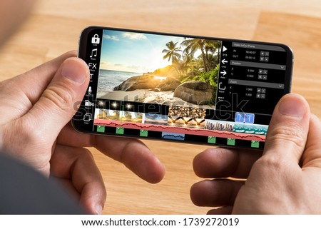 Editing Videos On Mobile Phone Using Video Editor App Royalty-Free Stock Photo #1739272019