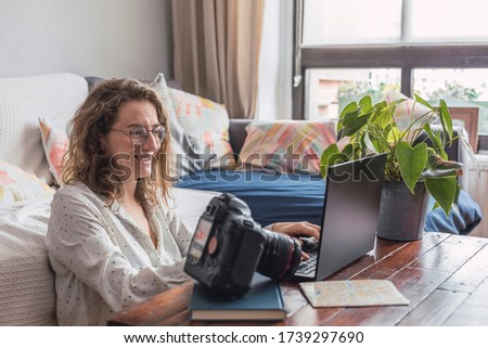 Smiling female photographer edits her photographs at home.