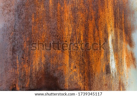 Rusty metal background. The texture of the metal. Beautiful unusual background. Rusty painted metal wall. Rusty old background with streaks of rust. Rust stain.