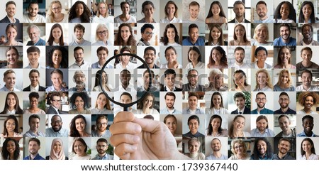 Male hand of hr manager, employer holding magnifying glass choosing finding african job candidate among many multiracial professional people faces collage. Staff recruitment, human resource concept.