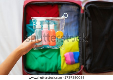 Tourist putting a toiletry bag with liquids in the suitcase. Concept of toiletry bag in the suitcase. Royalty-Free Stock Photo #1739380088