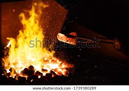 Forging the molten metal, making of an axe, traditional smithy Royalty-Free Stock Photo #1739380289