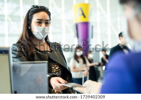 Asian female traveler giving passport to customer check in officer at airline service counter. Woman wearing face mask when traveling by airplane transportation to prevent covid19 virus pandemic. #1739402309