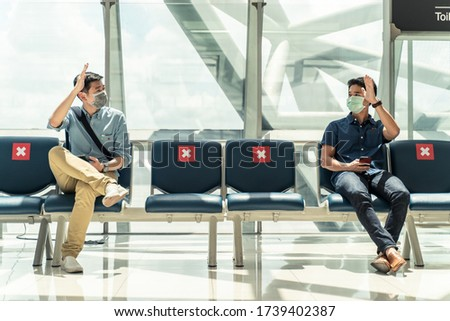 Social distancing, two men wearing face mask sitting keeping distance away from each other to prevent covid19 infection during pandemic. Empty chair seat red cross shows avoidance in airport terminal. Royalty-Free Stock Photo #1739402387