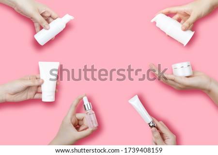Skincare routine step for healthy skin - Woman hands holding foam, essential oil, serum, lotion, cream and lip balm packaging on pink background. Beauty and cosmetic concept. Copy space. #1739408159