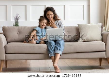 Happy mother and laughing little daughter looking at laptop screen, sitting on cozy couch, spending leisure time in living room, watching funny cartoons together, having fun with gadget at home