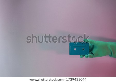 Green Hand holding audio cassette tape in the color light. Beautiful minimal in neon light. Minimalism retro style concept. Background pattern for design.