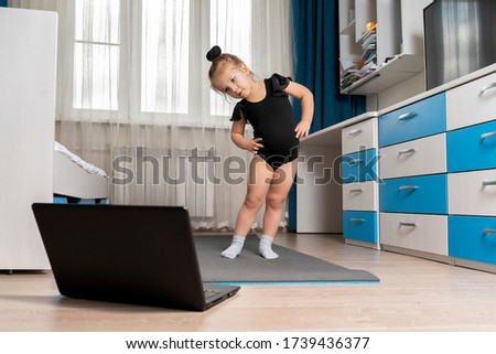 online rhythmic gymnastics. girl preschooler engaged in physical education with a trainer online
