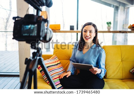 Handsome woman blogger hosting and recording video show and streaming it to the internet and world network, using camera with microphone and tablet computer
