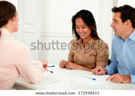 Portrait of young couple working with financial advisor while smiling and sitting on assistance workplace #173948615