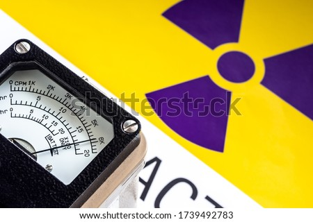 Hand-held radiation survey instrument detecting at the radioactive material symbol on label #1739492783
