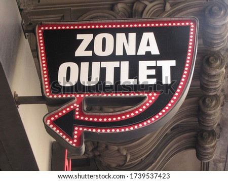 "Sign with the text translation: ""Outlet zone"". Arrow and words on a store sign placed on the facade of a building facing the street surrounded by red neon lights and a classic architecture background."