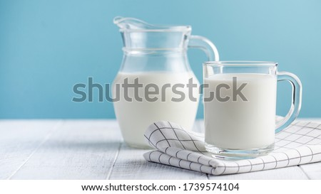 Banner of a glass of milk, a jug of milk on blue background. The concept of farm dairy products, milk day. Copy space. Royalty-Free Stock Photo #1739574104