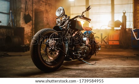 Custom Bobber Motorbike Standing in an Authentic Creative Workshop. Vintage Style Motorcycle Under Warm Lamp Light in a Garage. Royalty-Free Stock Photo #1739584955