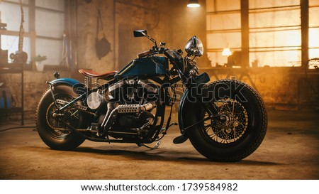 Custom Bobber Motorbike Standing in an Authentic Creative Workshop. Vintage Style Motorcycle Under Warm Lamp Light in a Garage. Royalty-Free Stock Photo #1739584982