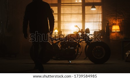 Custom Bobber Motorbike Standing in an Authentic Creative Workshop. Silhouette of a Rider Coming to a Bike. Vintage Style Motorcycle Under Warm Lamp Light in a Garage. Royalty-Free Stock Photo #1739584985