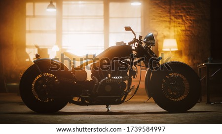 Custom Bobber Motorbike Standing in an Authentic Creative Workshop. Vintage Style Motorcycle Under Warm Lamp Light in a Garage. Profile View. Royalty-Free Stock Photo #1739584997
