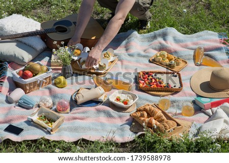 Young people doing picnic  in park - Group of happy friends having fun during the weekend outdoor - Friendship, food and drink, funny activities and youth lifestyle concept