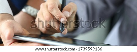 Man holds stylus and puts signature on tablet. Signing documents on an electronic touch device. Ability to quickly sign. Handle with special silicone tip. Ouch touch surface monitor
