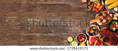 Summer BBQ or picnic food corner border over a rustic wood banner background. Assorted grilled meats, vegetables, fruits, salad and potatoes. Overhead view with copy space.