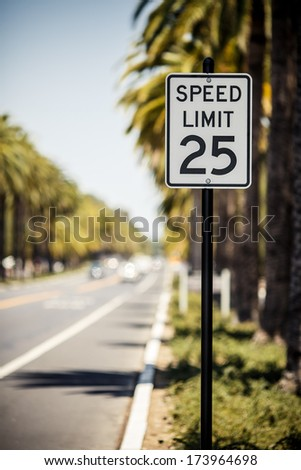 Speed Limit 25 sign on the road with palms, USA