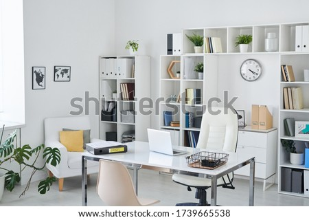 Office of business person with desk, armchair of professional, chair for clients, shelves, clock, green plant and two pictures on wall Royalty-Free Stock Photo #1739665538