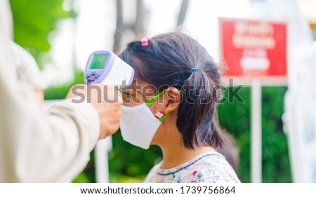 temperature check in school kid girl at school.Open school first health check up measurement.Asian girl measuring body temperature and wearing a face mask before go back to school.Healthcare medical. #1739756864