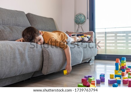 Bored child playing with blocks at home
