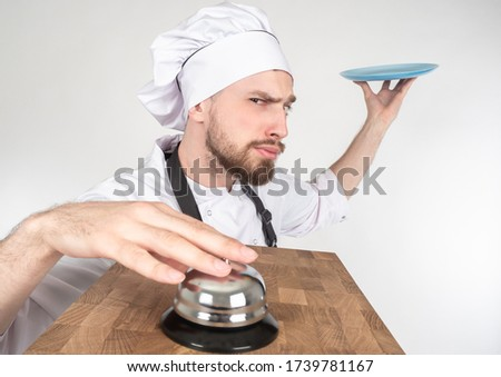 Comic picture about the service in the restaurant. The chef with plate rings the bell for the waiter. The bearded cook presses a button and makes faces. The waiter is fooling around.