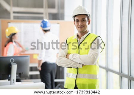 Portrait photo of young smart Hispanic  engineer wearing safety helmet standing indoor of company office or construction site with colleague discussing about work in distance.